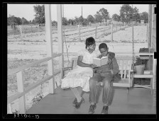 """""""Wife of FSA (Farm Security Administration) client reading book to her son on swing on her front porch,"""" Sabine Farms, Marshall, Texas. Library of Congress, https://www.loc.gov/pictures/item/2017783144."""