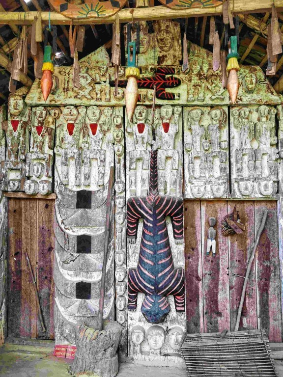 Paomai chief house – the carvings depict the tribe were fierce headhunters, standing over buried enemies and their heads in hand