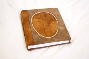 A journal, two tone goatskins leather with raised cross.