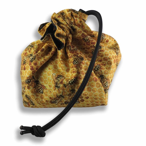 A drawstring reversible bag with bee pattern fabric.
