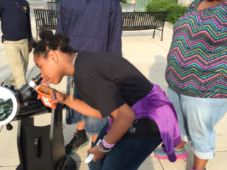 Teens from the West Englewood neighborhood view the Sun safely using a telescope.