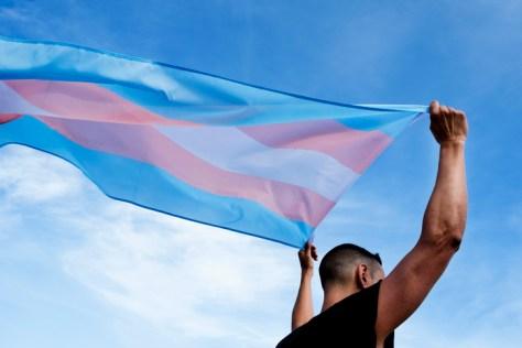 trans man holding trans flag