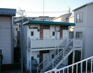 綱島街道から階段で降りる形の住宅地にある。後方に見えるのは東急線