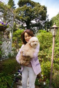 愛犬・杏奈(あんな)ちゃんとお待ちしています、と万里村れいさん。後ろには日吉の街を見守ってきた歴史ある樹齢80年の樫の木がそびえる