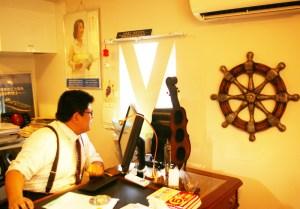 """音楽、海の仕事、そして日吉の街をこよなく愛する加賀さんの、""""日吉の縁の下の力持ち""""としての活動はこれからも続く(同事務所にて撮影)"""