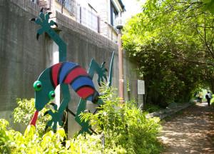 慶應ラグビー部グラウンド近くにある松の川緑道のシンボル・彫刻「爬虫類」ヤモリの像。「この道が、にんげんだけでなく、虫も鳥も、わしたち『爬虫類』も仲良く暮らせるような、楽しい草むらのある道になればと願っているんだ」との思いで設置された(2004年田辺光彰作)