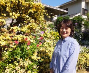 こぼれるかのように咲くモッコウバラと真島さん。「種」から草花を育てる技術を持つ真島さんは、他の団体や個人へ種や株を分け与え、その草花を育てる喜びを共に分かち合うことも多いという