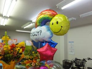 事務所内には訪問用の自転車も。岡野さんが関係した千葉県市川市の施設からのオープン祝いの花も届いていた