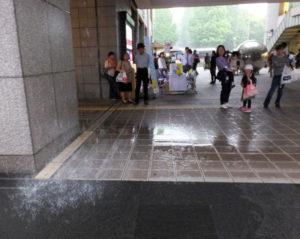 側溝からも水があふれ、道も歩けないほど。建物のへりからは滝のように水が降り注いていました(5月18日13時40分ころ)