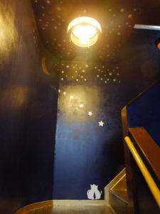 ロマンティックな優しさ醸(かも)す「劇場」をイメージしたという店舗2階に上がる階段部分。壁のイラストも店主・若宮さんのデザイン。ペンキも自身で塗り、建具も手作りしているという