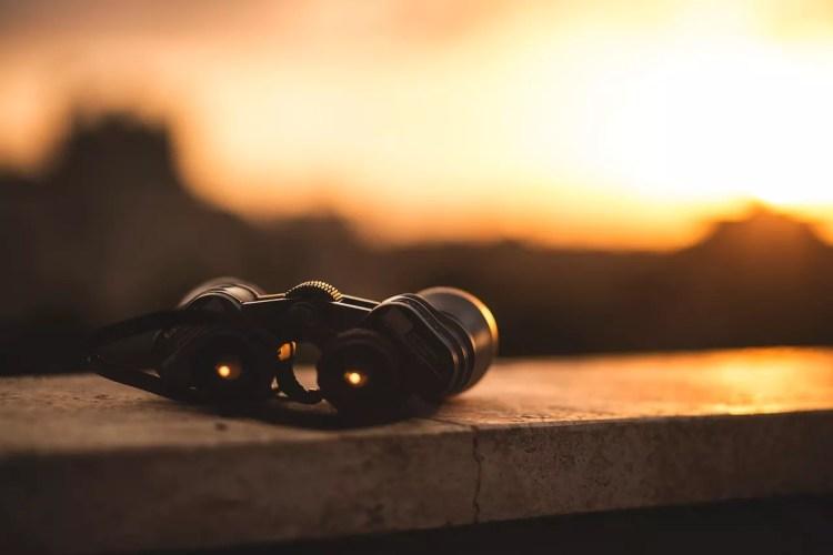 Binoculars on concrete in sunset