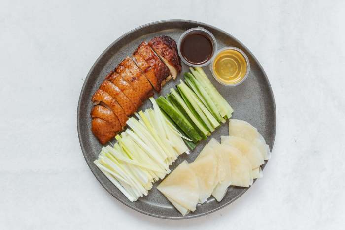 Sliced cucumber and meat on black plate