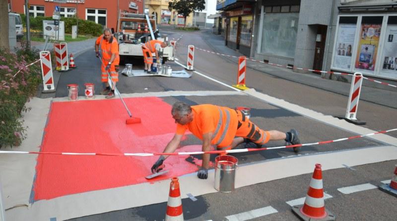 Mitarbeiter des Bauhofs der Stadt verteilen die rote Farbe auf der Fahrbahn der Grabenstraße. Insgesamt fünf Aufstellflächen für Radfahrerinnen und Radfahrer in der Grabenstraße sowie der Diezer Straße und der Dr.-Wolff-Straße sollen so gekennzeichnet werden. Bildhinweis: Stadt Limburg