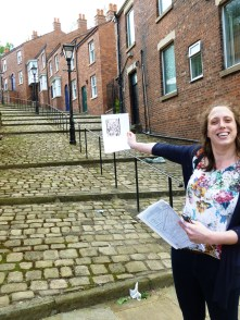 Juliette holds up an image of Lowry's 'Crowther Street' at the setting of the painting