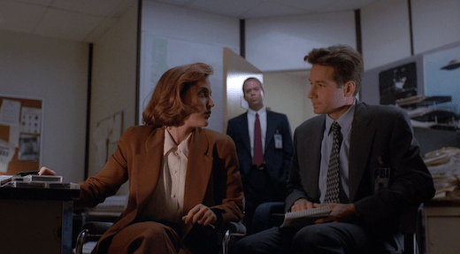 Mulder and Scully exchange a look while Jerry waits in the background.