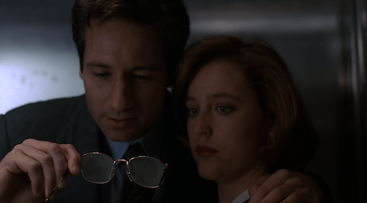 Mulder puts an arm around Scully and pulls her in to show her that he took two fingerprints from one of the ruffians on the surface of his eyeglasses.