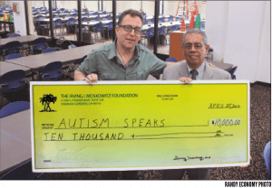 Matt Asner, Chairman of California Autism Speaks receives a $10,000 check from Sal Flores of the Moskowitz Foundation last week at the Hawaiian Gardens Bingo Club.