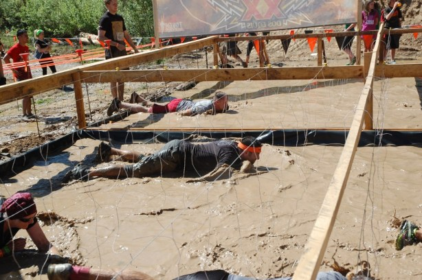 Steve Kopff, a two-year participant of the Tough Mudder in Beaver Creek, Colorado, moves through a watered-down muddy pit while dealing with electrical wires in the Electric Eel obstacle