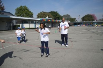 """Two-time National League Batting Champion Tommy Davis plays jump rope with students at Moffitt Elementary School in Norwalk as part of the Los Angeles Dodgers' """"Pitching In the Community"""" outreach event."""