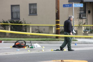An investigator from the Los Angeles County Sheriff's Department Homicide Division inspects the murder scene looking for clue at Studebaker Road and Farina Street in Norwalk on Tuesday afternoon. Brian Hews Photo