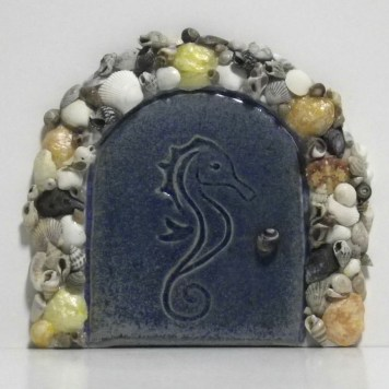 blue fairy door embossed with a seahorse, framed in seashells