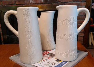 Three pitchers with slip trailed designs