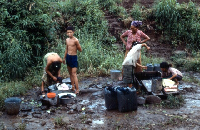 Gathering water from a well at Ban Vinai Refugee Camp, Thailand, 1980s