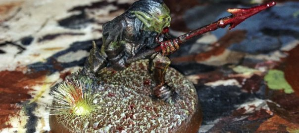 A Moria Goblin Spearman miniature soaked in blood.