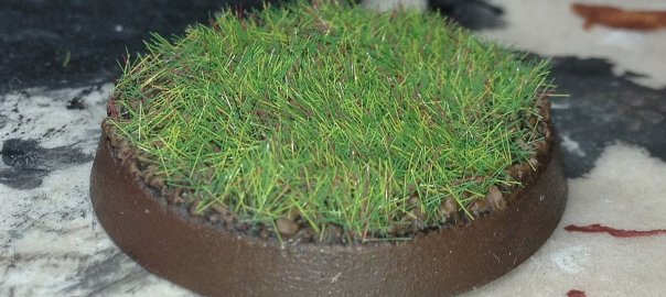 A Citadel miniature's base covered in grass.