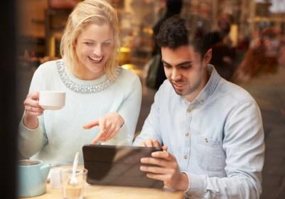 Couple Viewed Through window Using Digital Tablet