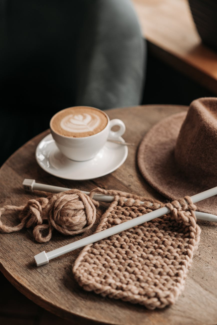 coffee drink beside a knitted material on wooden table
