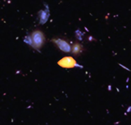 ALMA surveyed the Hubble Ultra Deep Field, uncovering new details of the star-forming history of the Universe. This close-up image reveals one such galaxy (orange), rich in carbon monoxide, showing it is primed for star formation. The blue features are galaxies imaged by Hubble. This image is based on the very deep ALMA survey by Manuel Aravena, Fabian Walter and colleagues, covering about one sixth of the full HUDF area.
