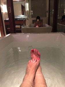 Image of a woman's feet in water taking a hot water bath and selfie in a bathtub in Alila Diwa Goa