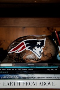 The current center piece for our living room. A Hawaiian coconut painted with the Patriots logo. Below that, a series of books from Colorado, Hawaii, and Alaska.