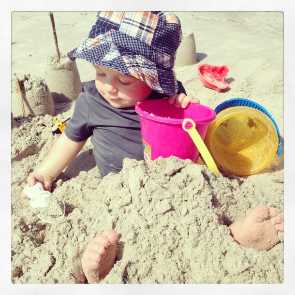 toddler buried in sand