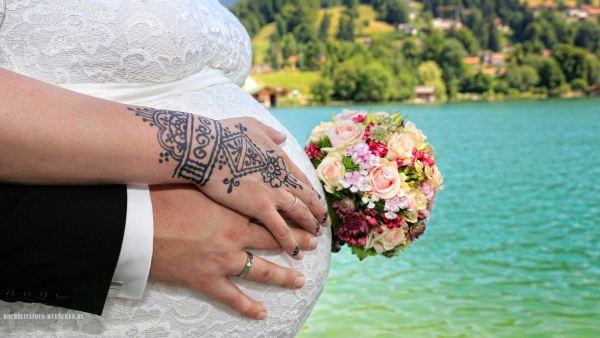 Hochzeitsbild mit Babybauch und Brautstraus