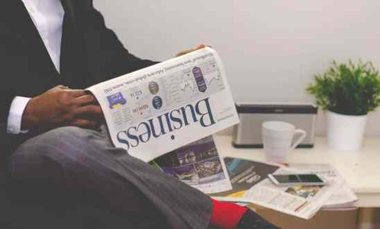 Black man with legs crossed reads the busines section of a newspaper