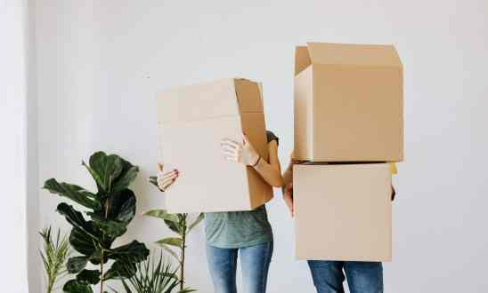 Two people carrying large cardbox boxes, their faces obscured behind the boxes