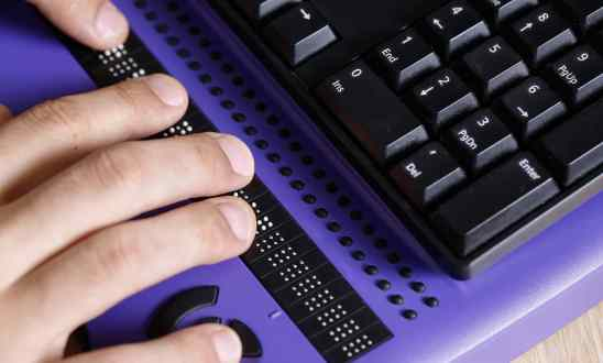 Blind person using computer with braille computer display and a computer keyboard.
