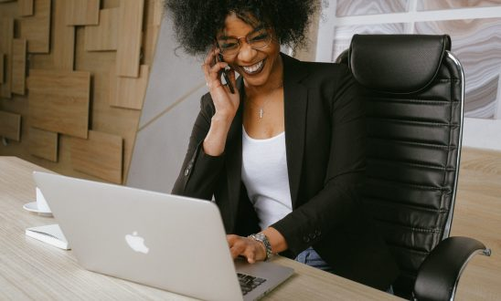 Black business professional on the phone while working at a laptop