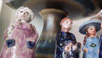 Mehrere Keramikfiguren, die Menschen darstellen und eine Vase stehen in einem Ladenregal.