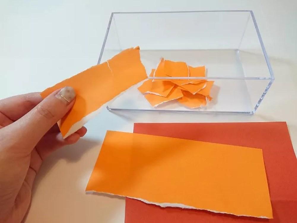 オレンジ色の折り紙をちぎる