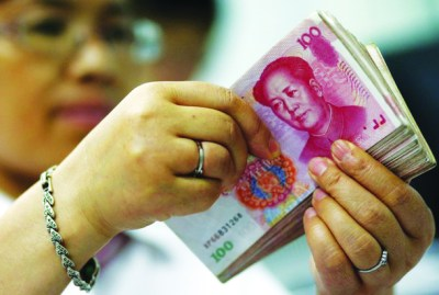 An employee counts yuan banknotes at a bank in Suining