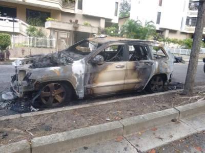Um carro incendiado na rua onde vive Maritza