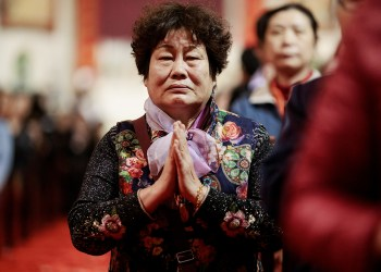 A woman prays during Holy Thursday Mass March 29 at the Cathedral of the Immaculate Conception in Beijing. (CNS photo/Damir Sagolj, Reuters)