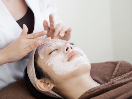 寝ながら顔にクリームを塗られている女性