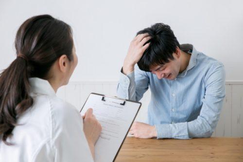 女性にカウンセリングを受けながら頭を抱えて悩んでる男性