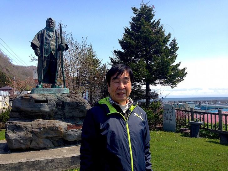 『オホーツク老人の像』の前に立つ、TBS『小沢昭一の小沢昭一的こころ』の坂本正勝プロデューサー