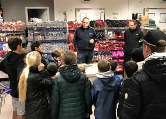 Købmand Johnny Borch fortæller eleverne fra Bjergmarkskolen om arbejdet med mindre madspild