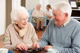 Elderly man and woman in a nursing home playing a game of dominos.